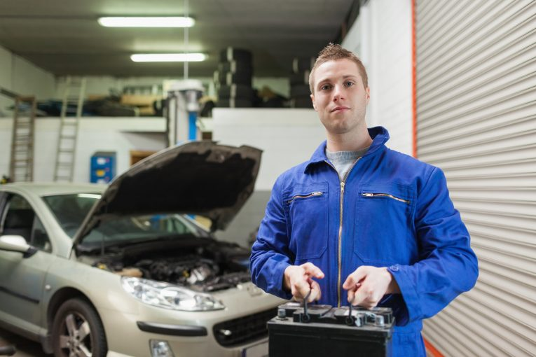 how to change a car battery. Portrait of male mechanic carrying car battery in workshop