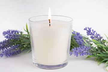 Candle in glass on white background with lavender