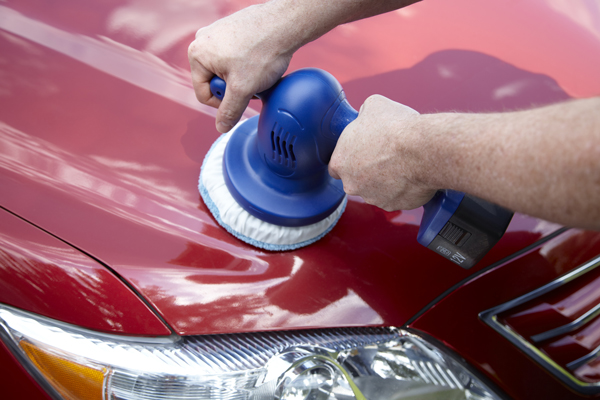 using a blue car buffer on a red automobile